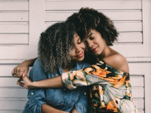Learning from Mistakes: Two women hugging.