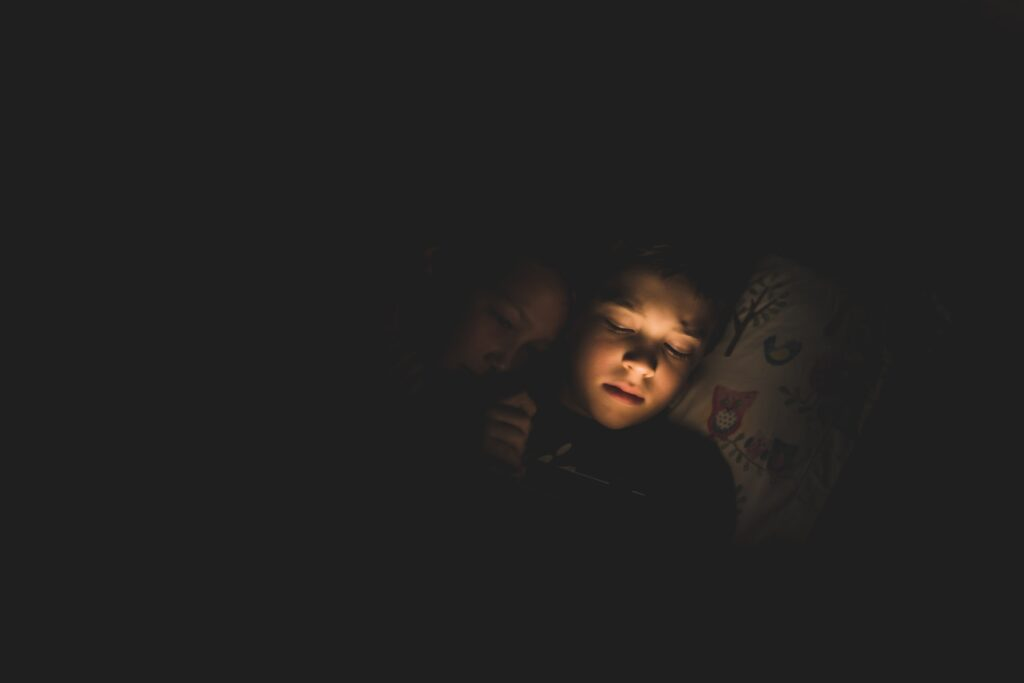 Dealing with Childhood Trauma in Adulthood. Image of two children on a bed in the dark.