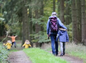Woman walking in nature with children | 7 Ideas to enjoy nature for better mental health.
